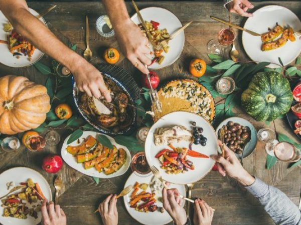 Traditional Thanksgiving or Friendsgiving holiday celebration party. Flat-lay of friends feasting at Thanksgiving Day table with turkey, pumpkin pie, roasted seasonal vegetables and fruit, top view (Traditional Thanksgiving)