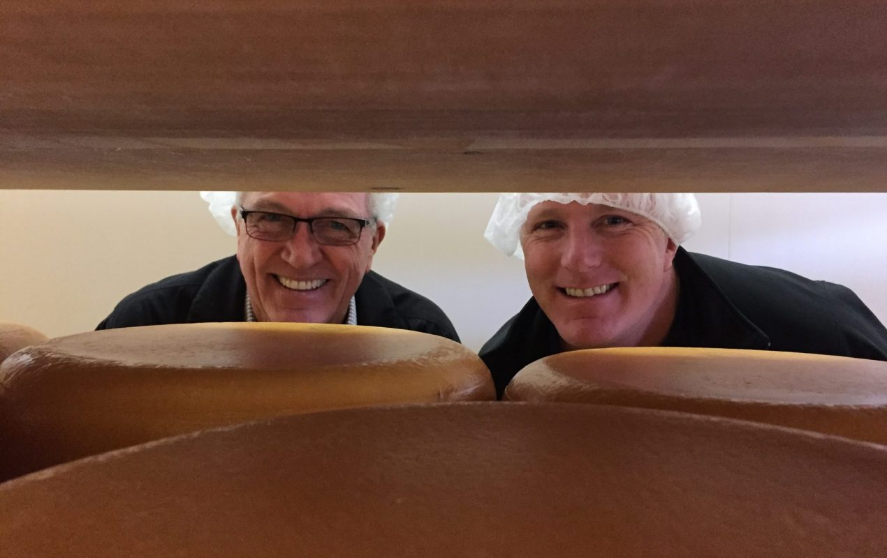two men hiding behind wheels of cheese at Mountainoak Cheese Co in New hamburg. Photo taken on a journey to the cheese trail with The Cheese Bar.