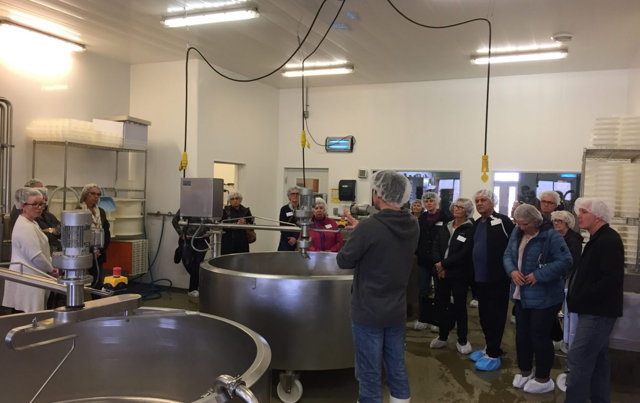 Shep from Gunn's Hill Artisan Cheese in his cheese making room describing the cheese making process to 16 guests standing in the sapce around two large stainless steel mixing vats