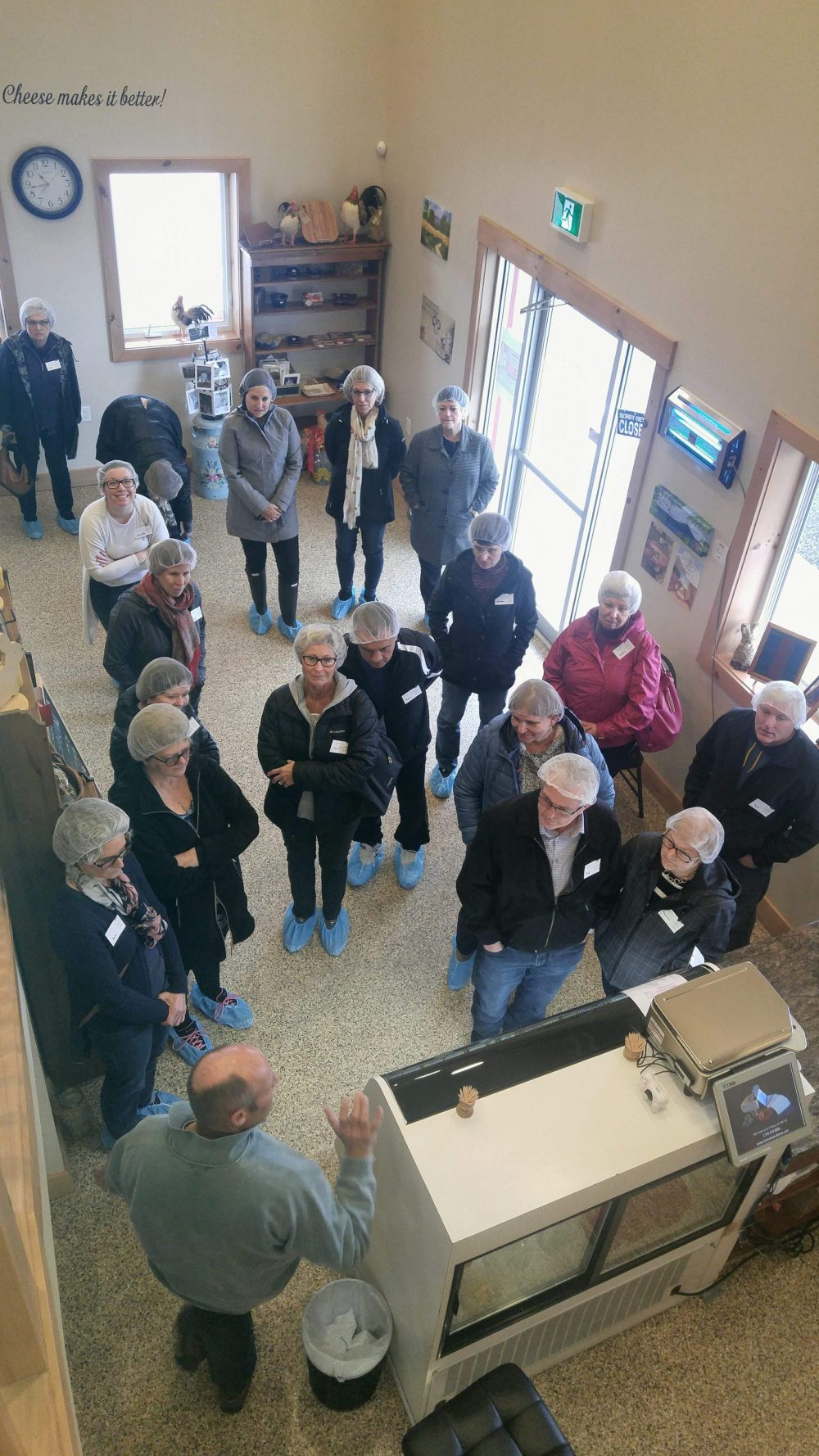 attendees preparing to go for a tour of stonetown cheese company in st mary's. All attendees are wearing blue booties and hair nets before in the main shop before entering in to the aging areas of the dairy.