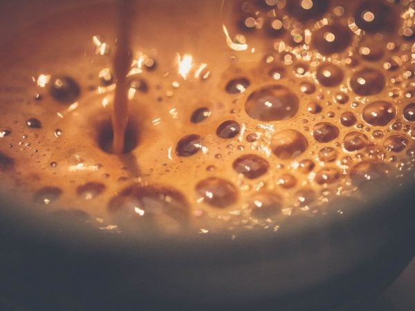 fresh coffee filling a coffee mug. Hot coffee streaming in to the froth. Small bubbles, dark brown creamy layering.