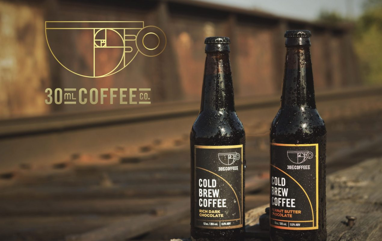30ml coffee co cold brew glass brown bottles on the right side of the image. Two flavours, peanut butter and rich dark chocolate. The brands logo with a coffee cup and the scientific chart for pi in the top left corner of the screen with the backdrop of railroad ties. A very rusty chic and bright image.